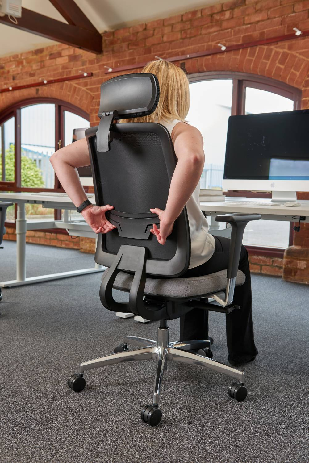 Woman Adjusting Integral Lumbar Support on Chair