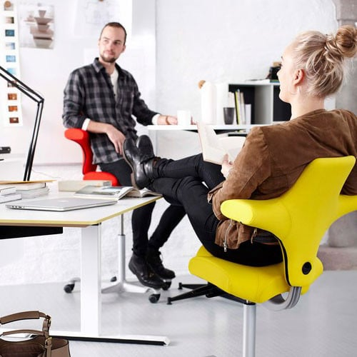 Woman-Leaning-Back-In-Yellow-HAG-Capisco-Office-Chair-Feet-On-Desk