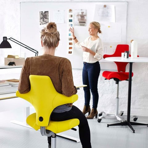 Woman-Sitting-In-Upholstered-HAG-Capisco-Yellow
