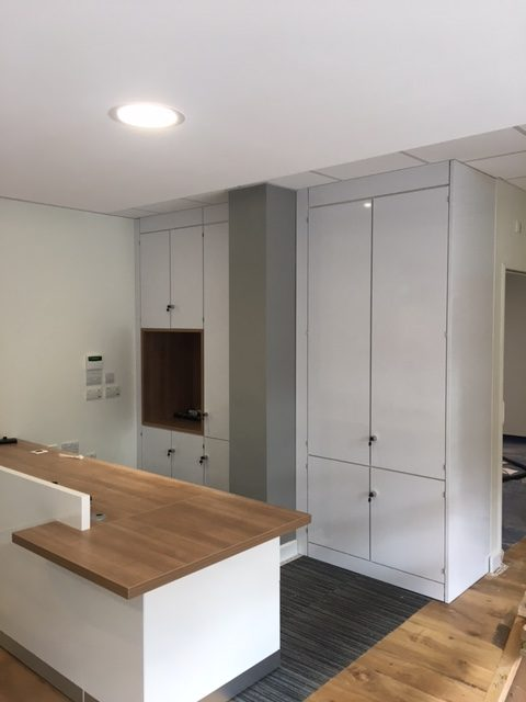 White Gloss Storage Wall in Reception Area